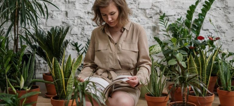 Woman reading a text on how to pack your plants next to her greenery.