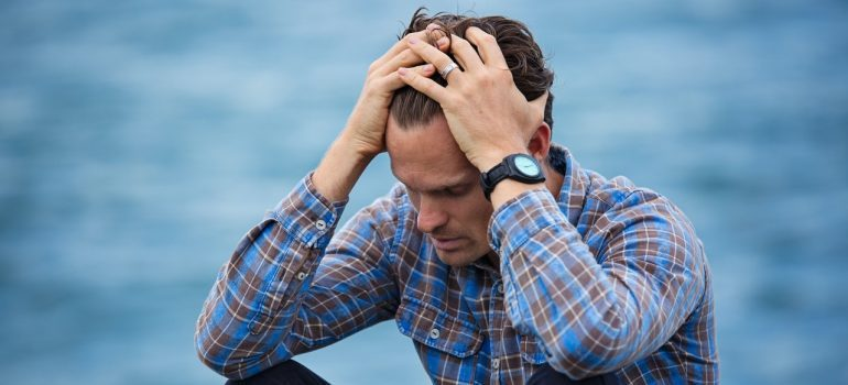 Stressed-out man holding his head in his hands.